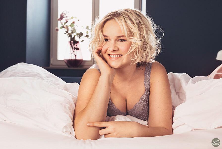 Lachende Frau liegt in Ulla Dessous in ihrem Bett