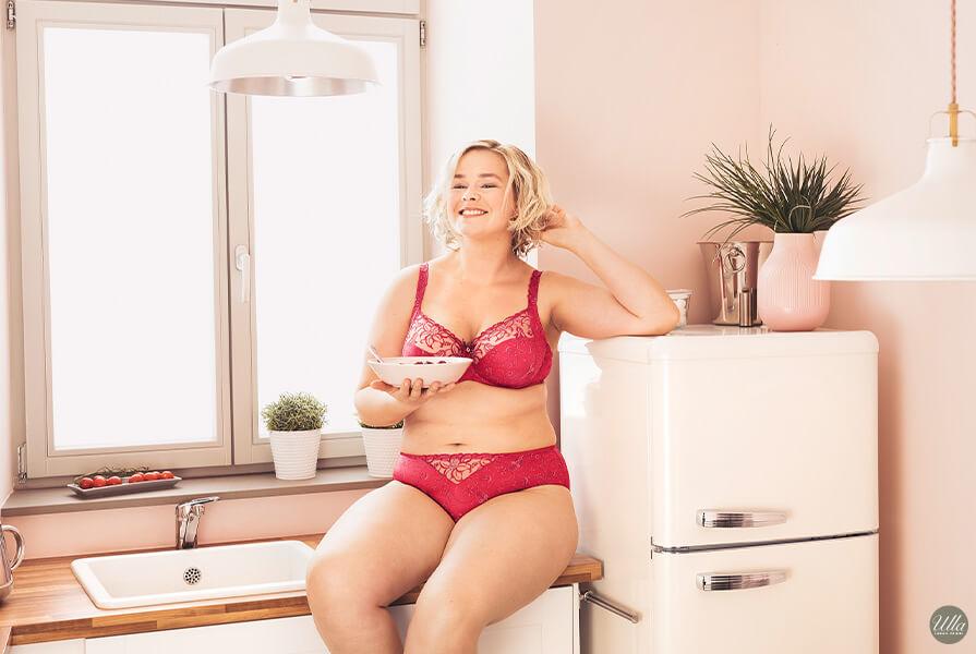 Plus Size Frau sitzt in roten Dessous von Ulla in der Küche
