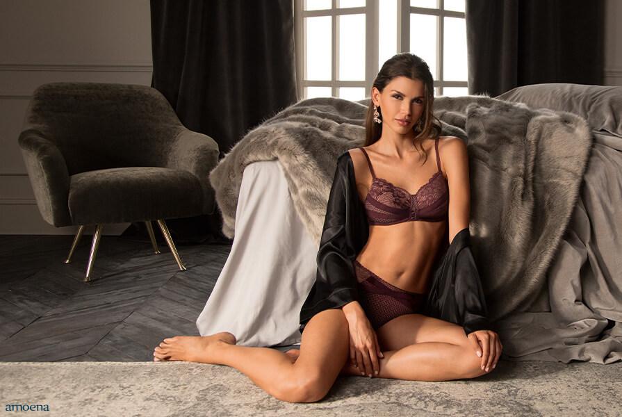 Frau in Dessous von Amoena vor Bett sitzend