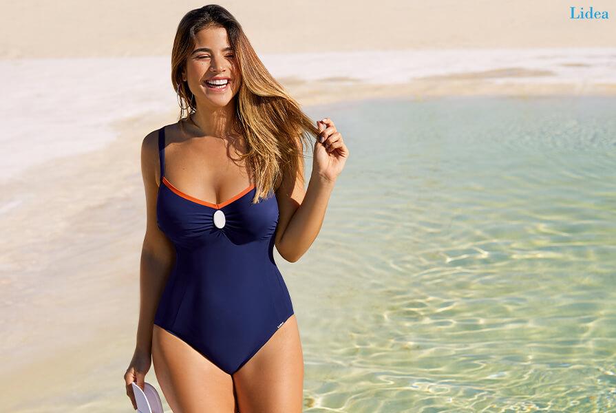 Lachende Frau in einem blauen Badeanzug von Lidea steht am Strand